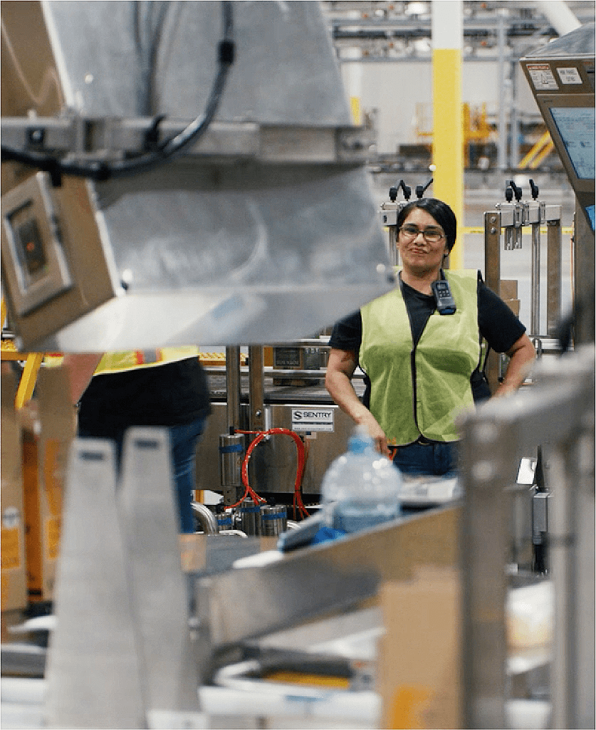 woman inside a factory smiling with hands on her hips