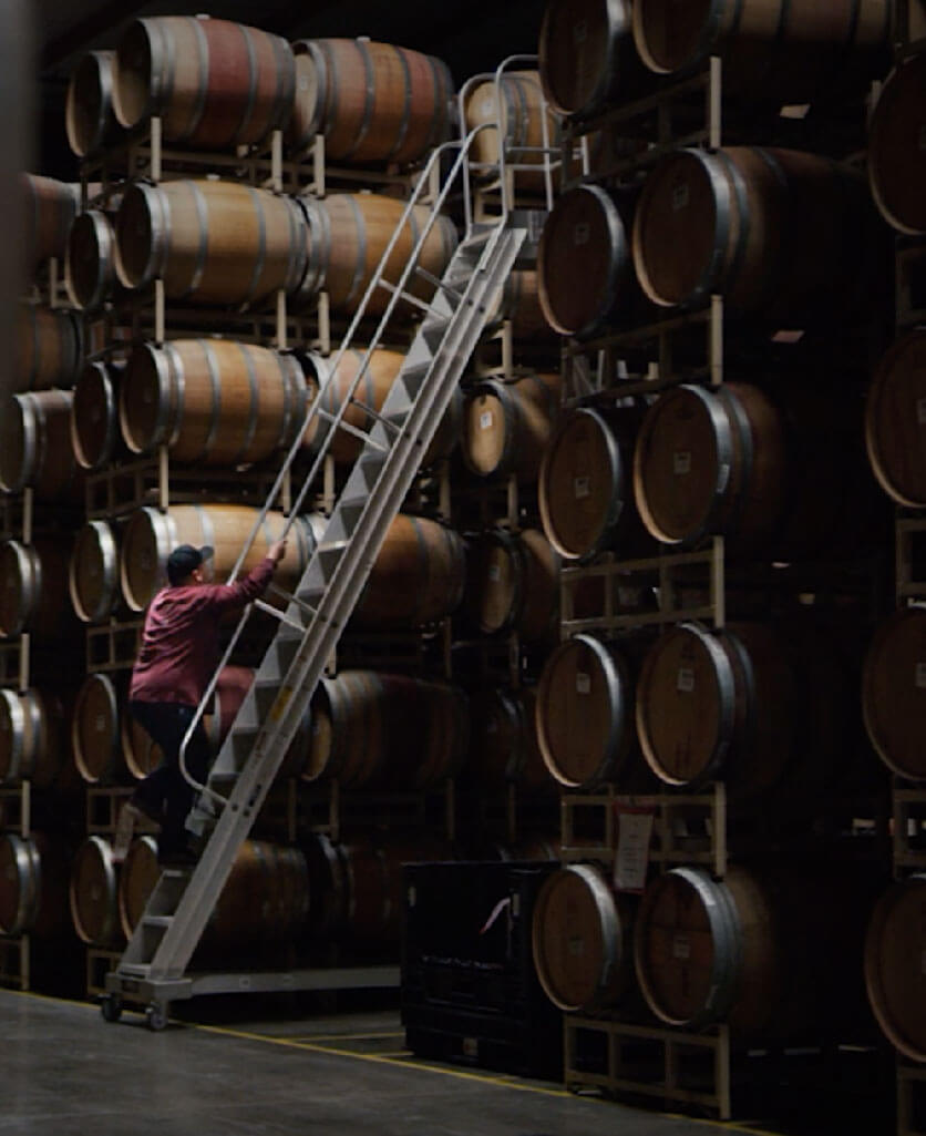 man climbing a ladder in a warehouse full of barrels