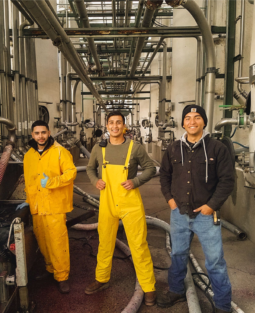 Three people standing inside a factory setting